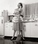 1955 --- 1950s Woman Housewife Standing In Kitchen Leaning On Broom --- Image by © American Stock Photography/ClassicStock/Corbis