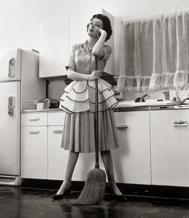 1950s Woman Housewife Standing In Kitchen Leaning On Broom